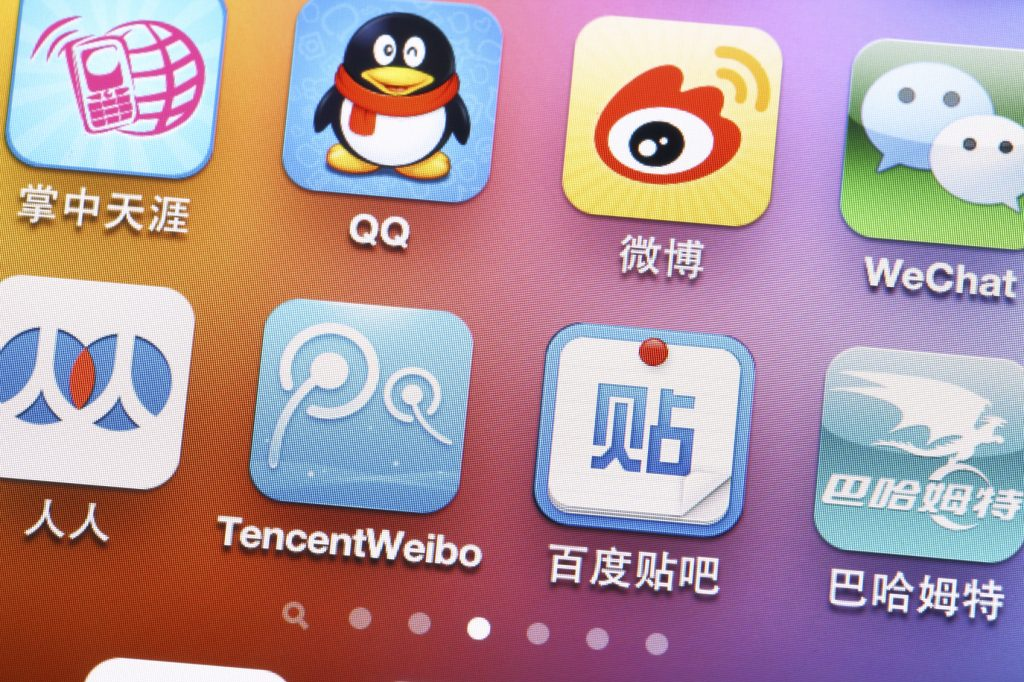Close up of iPhone screen showing common Chinese messaging apps QQ, Weibo and WeChat.
