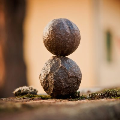 Two rocks perfectly balance on top of each other. Harmony.