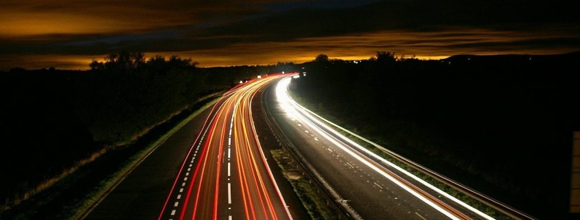 A highway at night shot with a long exposure to illustrate movement, specifically logistics.