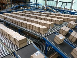 A warehouse conveyor line moving a large number of cardboard packaging boxes.