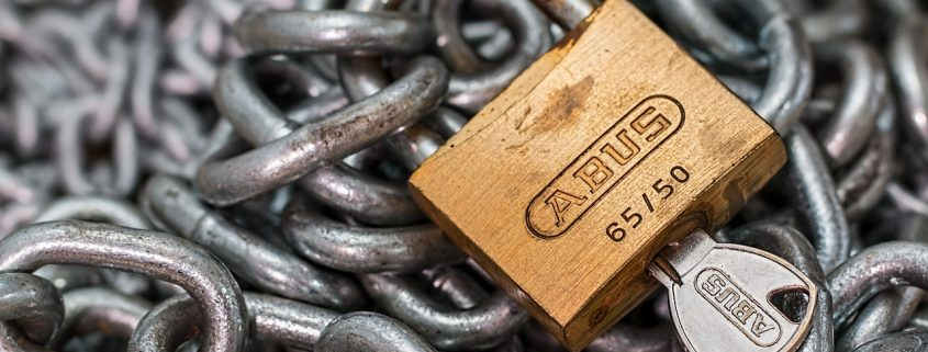 A padlock, with a key, and a large coil of chains to represent security.