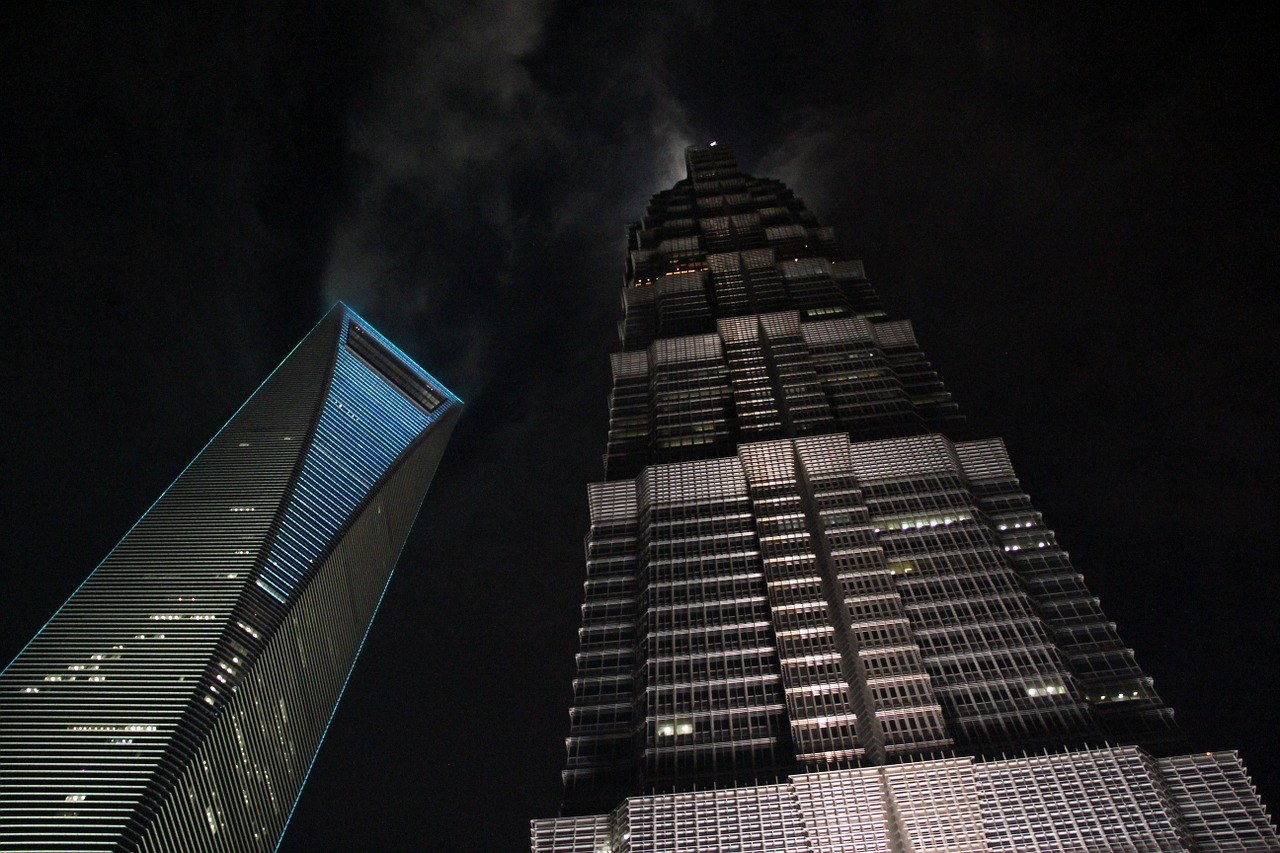 An upward shot of two skyscrapers in Shanghai at night.