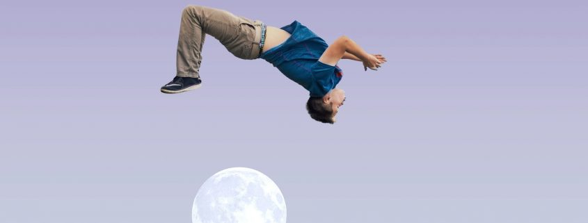 Agile. Man jumping athletically, framed over the moon.